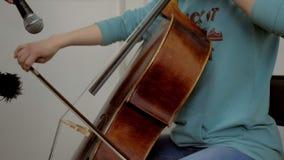 Muchacha joven del músico que juega con el violoncello del violoncelo almacen de video