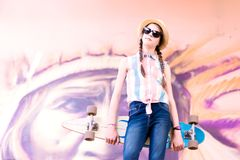 Muchacha joven del monopatín que sostiene su longboard al aire libre Imágenes de archivo libres de regalías