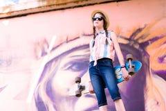 Muchacha joven del monopatín que sostiene su longboard al aire libre Foto de archivo