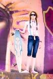 Muchacha joven del monopatín que sostiene su longboard al aire libre Fotos de archivo libres de regalías