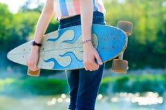 Muchacha joven del monopatín que sostiene su longboard al aire libre en puesta del sol Fotografía de archivo libre de regalías