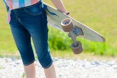 Muchacha joven del monopatín que sostiene su longboard al aire libre en puesta del sol Fotos de archivo libres de regalías