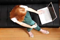 Muchacha joven del pelirrojo con un ordenador portátil Imagen de archivo libre de regalías