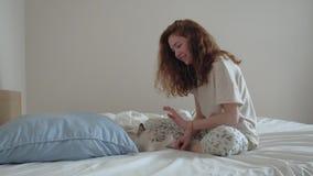 Muchacha joven del pelirrojo que juega con un gatito en cama metrajes