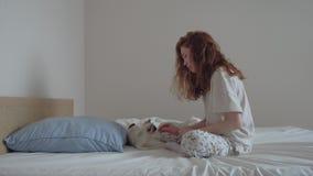 Muchacha joven del pelirrojo que juega con un gatito en cama almacen de video