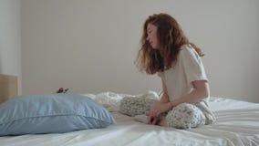 Muchacha joven del pelirrojo que juega con un gatito en cama almacen de metraje de vídeo