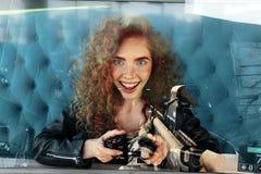 Muchacha joven del pelirrojo que juega el juego y la sonrisa de la pistola de los fps Foto de la exposición doble Imagen de archivo libre de regalías