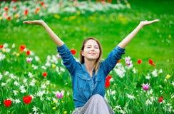 Muchacha joven del pelirrojo que se sienta en el prado de los tulipanes Imagen de archivo libre de regalías