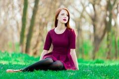 Muchacha joven del pelirrojo que se sienta en hierba verde Fotos de archivo libres de regalías