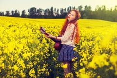 Muchacha joven del pelo del jengibre en el estilo 70s con la guitarra acústica Foto de archivo