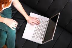Muchacha joven del Redhead con una computadora portátil Imágenes de archivo libres de regalías