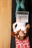 Muchacha joven del Redhead que practica surf en el sofá Foto de archivo libre de regalías