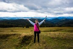 Muchacha joven del viajero encima de una colina con una hermosa vista de las montañas imagen de archivo
