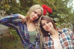 Muchacha joven dos atractivos alegres y morenita rubias que presentan contra el fondo de la naturaleza, los vaqueros que llevan y Fotos de archivo