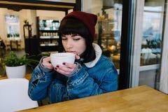 Muchacha joven elegante del inconformista que se sienta en un café de consumición del café y que mira en la ventana Imagen de archivo libre de regalías