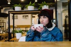 Muchacha joven elegante del inconformista que se sienta en un café de consumición del café y que mira en la ventana Imagenes de archivo