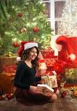 Muchacha joven, feliz cerca del árbol de navidad con los presentes Fotos de archivo