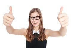 Muchacha joven feliz del adolescente que muestra los pulgares para arriba aislados Foto de archivo libre de regalías