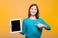 Muchacha joven feliz del estudiante poiting en una tableta digital que ella es Imagen de archivo