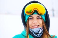 Muchacha joven feliz del snowboarder en gafas de la snowboard Foto de archivo libre de regalías