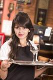 Muchacha joven hermosa de la camarera que sirve una bebida Imagenes de archivo