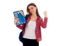 Muchacha joven hermosa de los estudiantes con la mochila y carpetas para los cuadernos en sus manos que sonríen en la cámara aisl Imagen de archivo