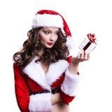 Muchacha joven hermosa de Papá Noel con el pequeño regalo en el fondo blanco Fotos de archivo