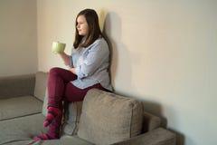 Muchacha joven hermosa del adolescente en casa que fija en el sofá Imagenes de archivo