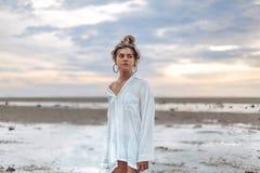 Muchacha joven hermosa del estilo del boho en la playa en la puesta del sol na joven Imagen de archivo