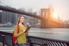 Muchacha joven hermosa del estudiante que camina en la ciudad con la mochila usando la PC de la tableta al aire libre en Nueva Yo Fotos de archivo libres de regalías