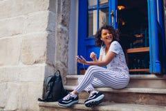 Muchacha joven hermosa del estudiante que usa el teléfono elegante y escuchando la música que se sienta por el café Imagen de archivo