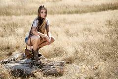 Muchacha joven hermosa del hippy que se sienta en un tocón de árbol en el mediodía Fotos de archivo libres de regalías