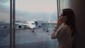 Muchacha joven, hermosa que habla en el teléfono en terminal de aeropuerto contra la perspectiva de un avión almacen de metraje de vídeo