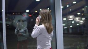 Muchacha joven, hermosa que habla en el teléfono en un terminal de aeropuerto vacío contra la perspectiva de un avión metrajes