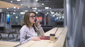 Muchacha joven, hermosa que habla en el tel?fono que se coloca en una tabla con un ordenador port?til y una taza de caf? en el ae metrajes