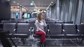 Muchacha joven, hermosa que habla en el tel?fono en un terminal de aeropuerto vac?o almacen de video