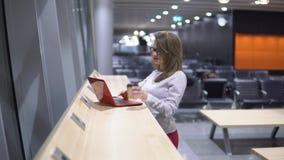 Muchacha joven, hermosa que trabaja detrás de un ordenador portátil y café de consumición en una tabla de madera en un terminal d metrajes