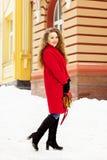 Muchacha joven, hermosa y elegante del pelo rubio en capa roja y con el bolso que camina a través de las calles de la ciudad Moda Foto de archivo