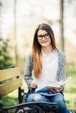 Muchacha joven hermosa y feliz del estudiante que se sienta en banco, sosteniendo el libro en sus manos, sonriendo y mirando en l Imagenes de archivo