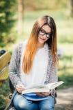 Muchacha joven hermosa y feliz del estudiante que se sienta en banco, sosteniendo el libro en sus manos, sonriendo y mirando en l Imagen de archivo