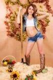 Muchacha joven linda del granjero que trabaja con el bieldo en un pajar Fotos de archivo libres de regalías