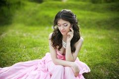 Muchacha joven morena atractiva de la novia que se sienta en hierba verde en s Fotos de archivo libres de regalías