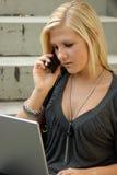 Muchacha joven, rubia con la computadora portátil y teléfono móvil. Fotografía de archivo libre de regalías