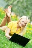 Muchacha joven sonriente del estudiante con la computadora portátil Fotos de archivo libres de regalías