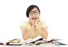 Muchacha joven sonriente del estudiante que piensa con el libro en el escritorio Imágenes de archivo libres de regalías