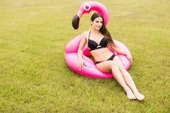 Muchacha joven y atractiva que se divierte y que ríe y que se divierte en la hierba cerca de la piscina en un flamenco rosado inf imagenes de archivo