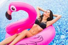 Muchacha joven y atractiva que se divierte y que ríe en un colchón rosado gigante inflable del flotador de la piscina del flamenc imagenes de archivo