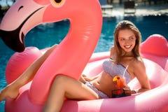 Muchacha joven y atractiva que se divierte y que ríe en un colchón rosado gigante inflable del flotador de la piscina del flamenc imagen de archivo libre de regalías