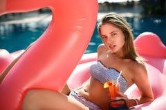 Muchacha joven y atractiva que se divierte y que ríe en un colchón rosado gigante inflable del flotador de la piscina del flamenc fotos de archivo