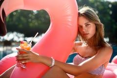 Muchacha joven y atractiva que tiene mentiras en el sol un colchón rosado gigante inflable del flotador de la piscina del flamenc fotografía de archivo libre de regalías